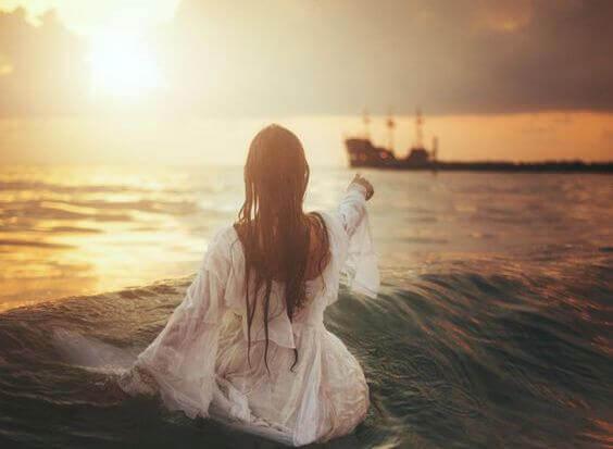 donna in riva al mare guarda barca perdersi