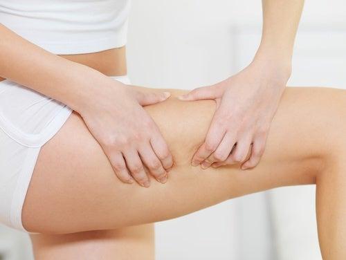 Donna controlla lo strato di grasso delle cosce