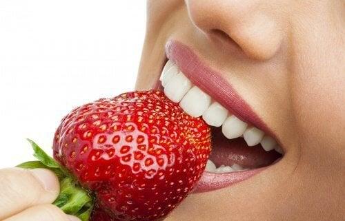 Denti sani che mordono una fragola