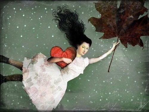 Donna che vola con cuore tra le mani e foglia