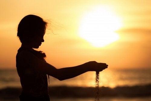 bambina con sabbia tra le mani al tramonto