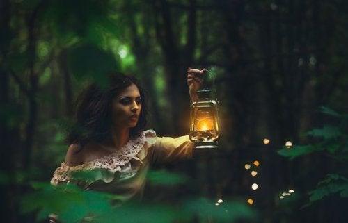 donna-con-lanterna-in-un-bosco
