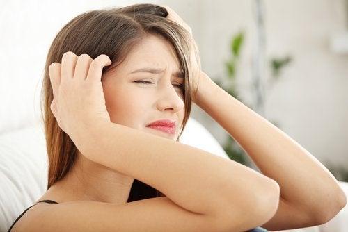 Ragazza con mal di testa e mani alle tempie
