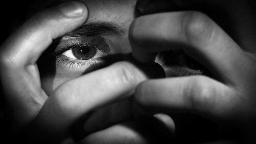 uomo che si nasconde il viso con le mani