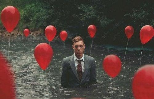 Uomo nel fiume con palloncini
