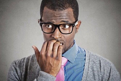 uomo ansioso che si mangia le unghie