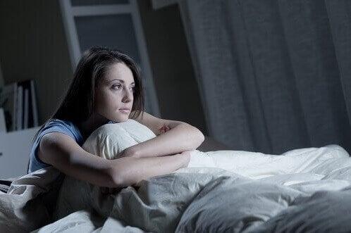 Donna con insonnia seduta nel letto