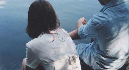 partner seduti vicini sul mare