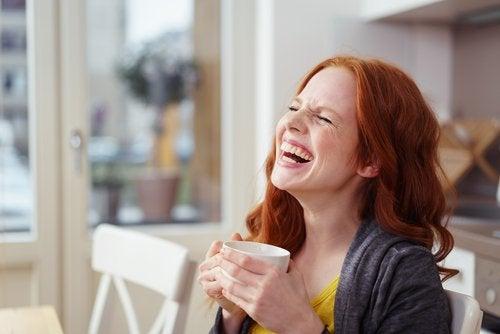 Donna con tazza di caffè ride