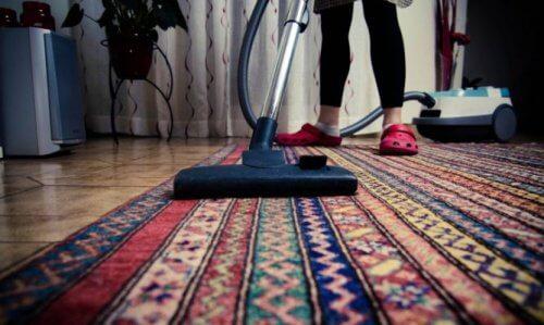 donna che passa l'aspirapolevere sul tappeto