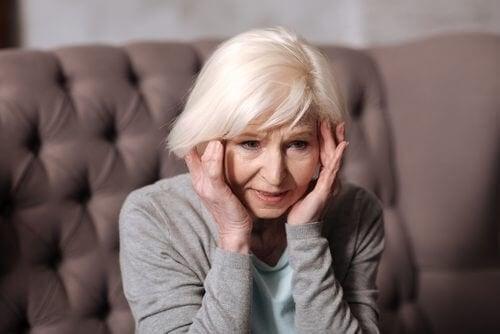 Donna anziana con mani sulle tempie