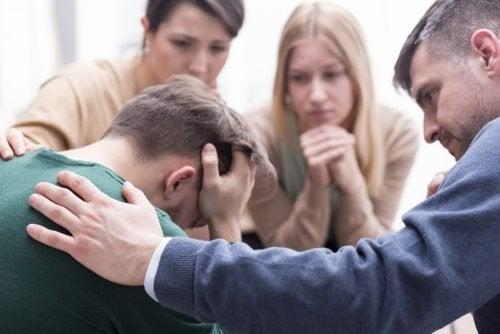 Amici consolano uomo vittima di maltrattamento psicologico