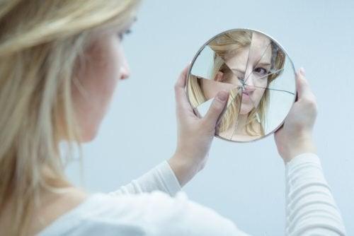 Donna che si specchia in uno specchio rotto