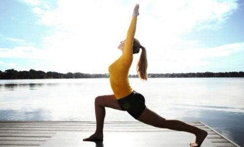 Ragazza esegue posizione yoga del guerriero