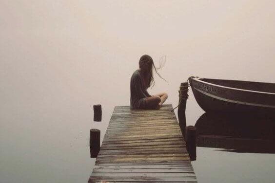 ragazza seduta da sola su un molo