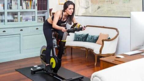 Trattare le vene varicose: donna che usa la cyclette in casa.
