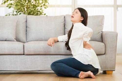 Donna con dolore alla schiena tra i sintomi della fibromialgia