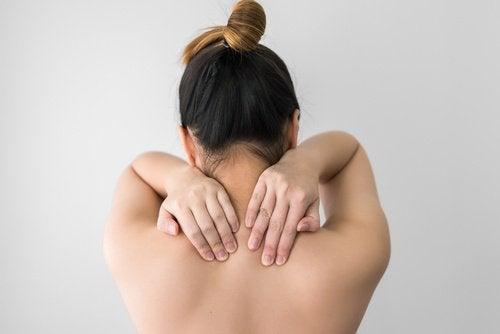 donna di spalle si massaggia la schiena