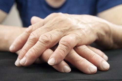 persona con mani sovrapposte sul tavolo