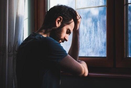 uomo stanco con la testa appoggiata alla finestra