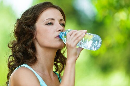 Ragazza che beve da bottiglia di plastica