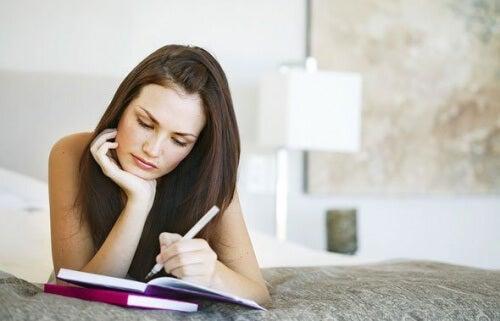 Donna che scrive sdraiata sul letto