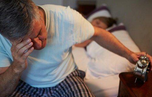 Uomo che soffre di insonnia guarda la sveglia