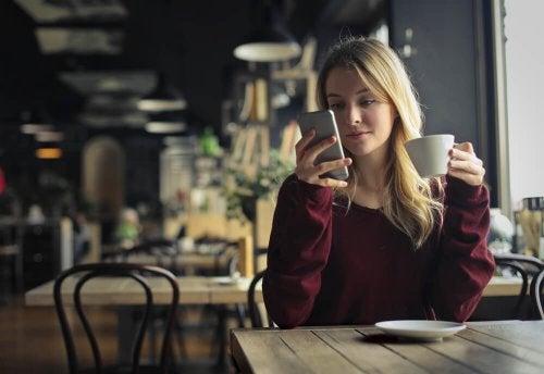 Ragazza beve un caffè e guarda il cellulare
