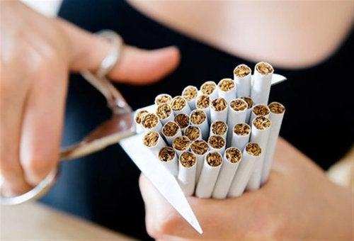 Ragazza taglia sigarette per smettere di fumare