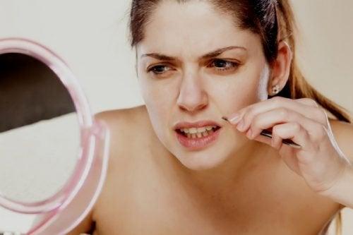 Ragazza usa la pinzetta per eliminare i peli del viso