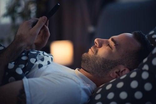 Ragazzo a letto guarda il telefono
