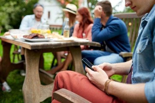Ragazzo guarda il cellulare isolato dal gruppo
