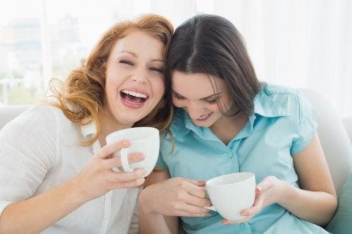 Amiche che ridono e bevono tè