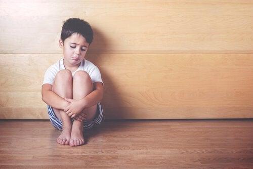 Bambino seduto da solo e triste