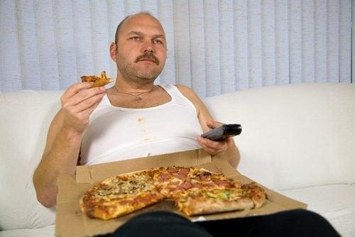 Uomo che mangia pizza sul divano