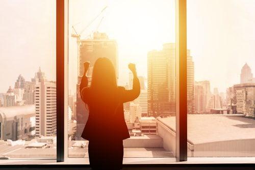 Donna di schiena davanti ad una finestra di un grattacielo