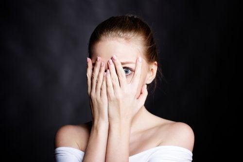 Donna che ha paura e nasconde il volto dietro alle mani