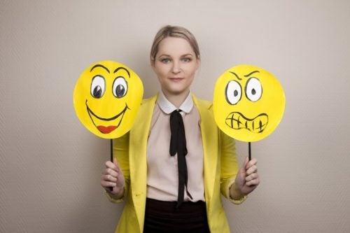 Donna che tiene cartelli con facce che mostrano emozioni opposte, rappresentando la sua capacità di gestire le emozioni