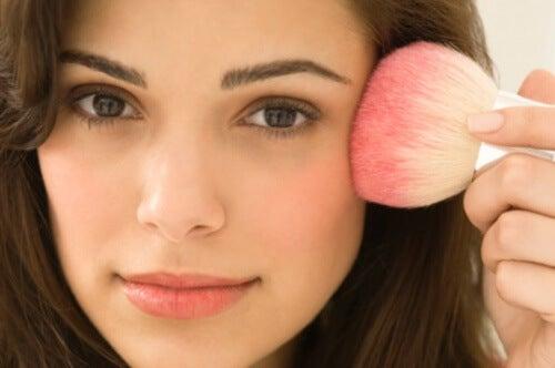 Primo piano di una donna che applica trucco sul volto con un pennello