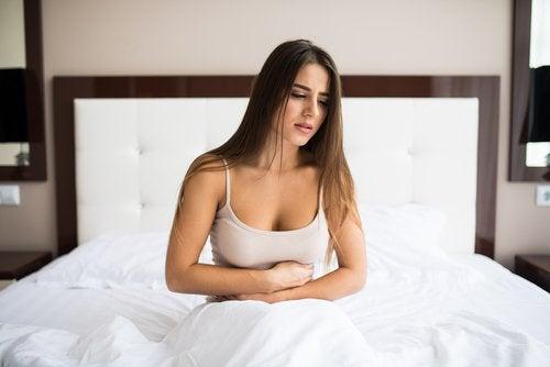 Ragazza sul letto con mal di pancia