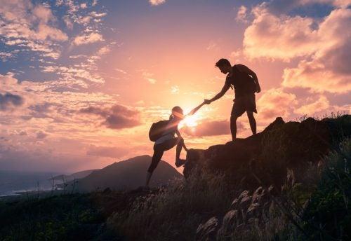 Un ragazzo che aiuta una ragazza in montagna, aiutandola a creare la resilienza