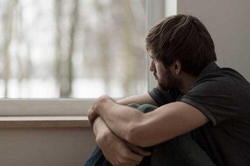 Ragazzo triste guarda fuori dalla finestra