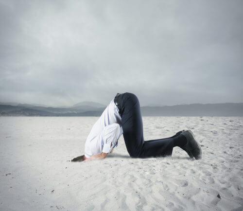Uomo che ha paura e nasconde la testa sotto alla sabbia