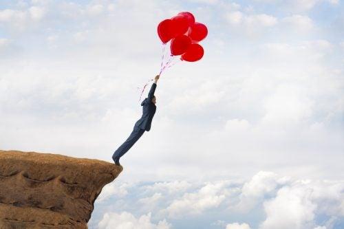 Le questioni irrisolte - Uomo su una rupe che sta per volare via trasportato da dei palloncini