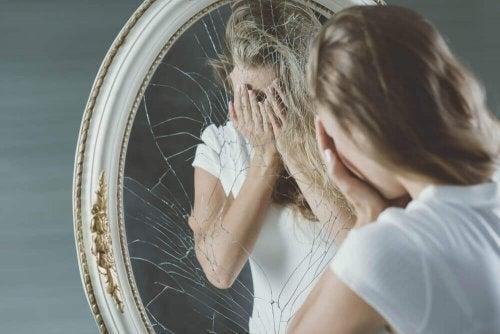Donna davanti ad uno specchio rotto che rappresenta il mentire a sé stessi