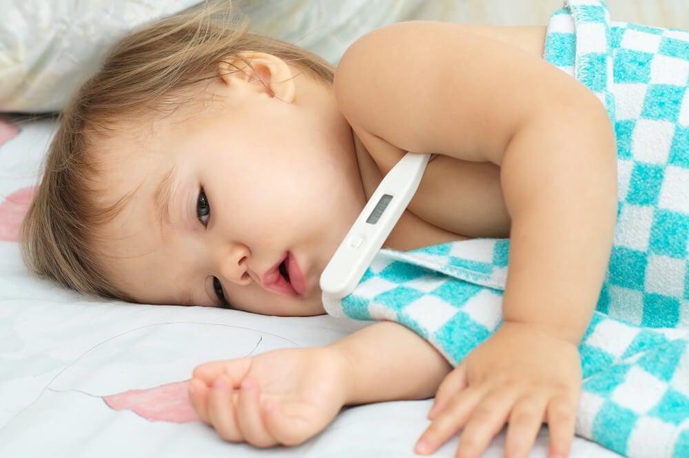 Bambina con il termometro per misurare la febbre
