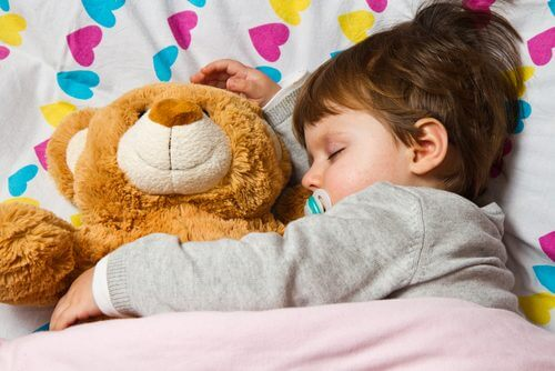 Bambino addormentato con il suo orsacchiotto