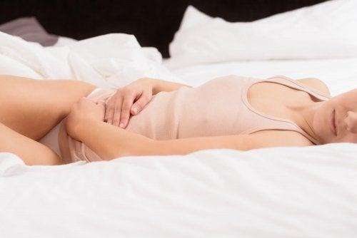 Donna a letto con dolore alle ovaie
