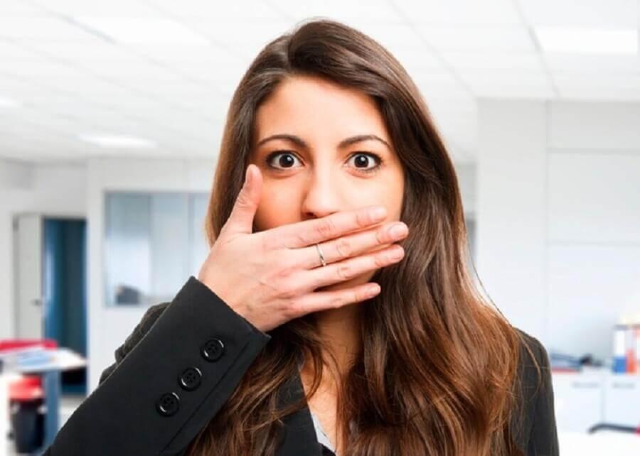 Donna che soffre di alitosi con mano davanti alla bocca