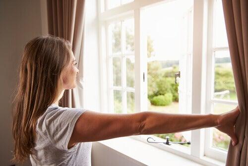 Donna che apre la finestra per realizzare pulizia energetica della casa